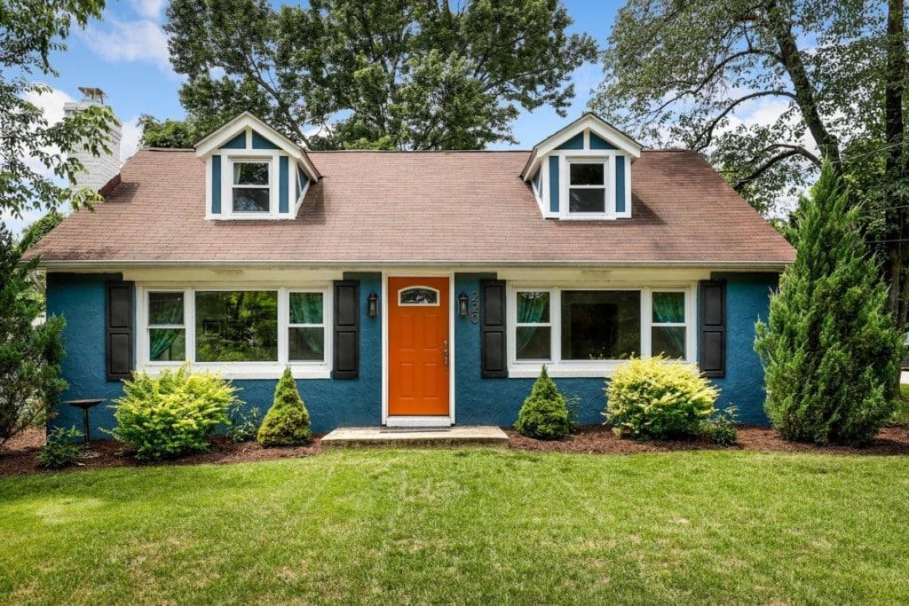 blue-house-front-yard-with-white-trim-orange-door